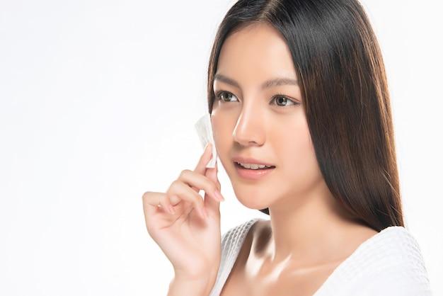 Kobieta do pielęgnacji skóry usuwająca makijaż twarzy za pomocą wacika., Premium Zdjęcia