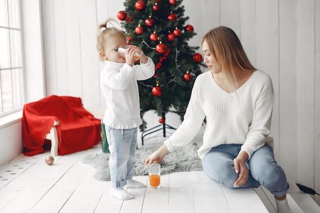 Kobieta Dobrze Się Przygotowuje Do świąt Bożego Narodzenia. Matka W Białym Swetrze, Bawić Się Z Córką. Rodzina Odpoczywa W świątecznym Pokoju. Darmowe Zdjęcia