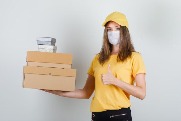 Kobieta Dostawy Trzymając Pudełka Z Kciukiem Do Góry W T-shirt, Spodnie I Czapkę, Maskę I Wyglądający Wesoło Darmowe Zdjęcia