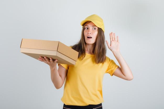 Kobieta Dostawy Trzymając Pudełko Z Ręką Przy Uchu W Koszulce, Czapce, Spodniach I Szuka Zainteresowania Darmowe Zdjęcia
