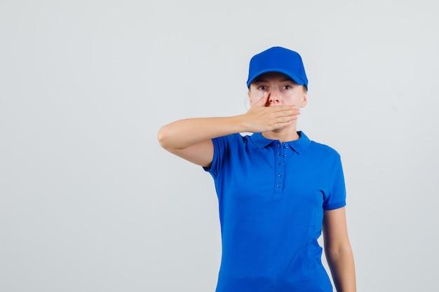Kobieta Dostawy W Niebieskiej Koszulce I Czapce, Trzymając Rękę Na Ustach I Patrząc Poważnie Darmowe Zdjęcia