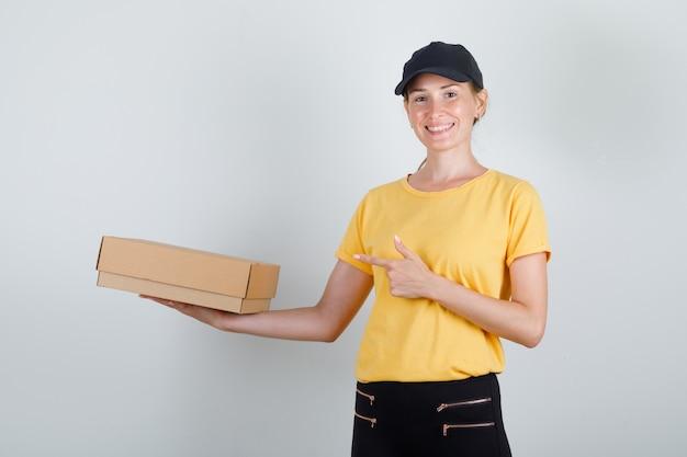 Kobieta Dostawy, Wskazując Palcem Na Karton W T-shirt, Spodnie, Czapkę I Patrząc Szczęśliwy Darmowe Zdjęcia