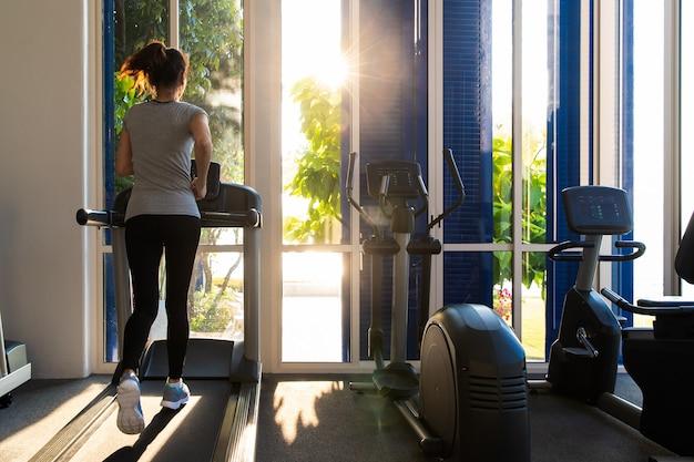 Kobieta działa w siłowni fitness na bieżni sprzęt do ćwiczeń. Premium Zdjęcia