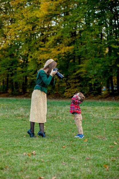 Kobieta fotograf fotografuje dziecko wydawać outside w parku Premium Zdjęcia