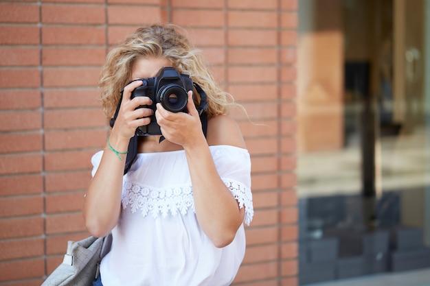 Kobieta fotograf pracujący w środowisku miejskim Premium Zdjęcia
