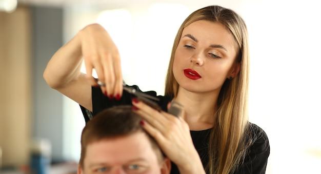 Kobieta Fryzjerka Cięcia Włosów Klienta Mężczyzny. Salon Fryzjerski Kobieta Trzymając W Ręku Nożyczki. Młody Stylista Dokonywanie Fryzury Dla Męskiego Klienta. Facet Robi Fryzurę W Salonie Piękności. Kosmetyczka Do Stylizacji Włosów Premium Zdjęcia