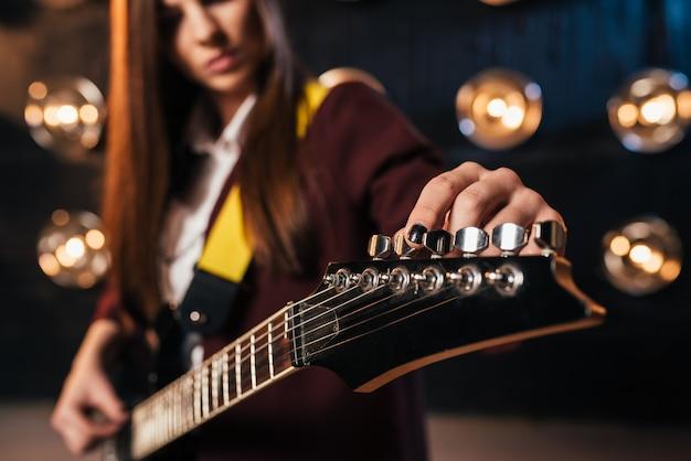 Kobieta Gitarzysta Rockowy W Garniturze Nastraja Gitarę Premium Zdjęcia