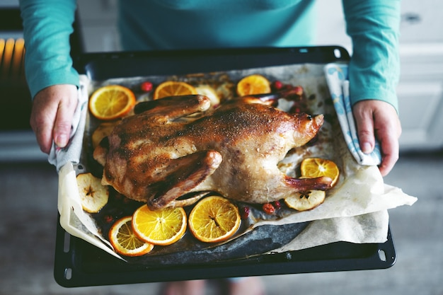 Kobieta Gotowanie Kaczki Z Warzywami I Wkładanie Jej Z Piekarnika. Darmowe Zdjęcia