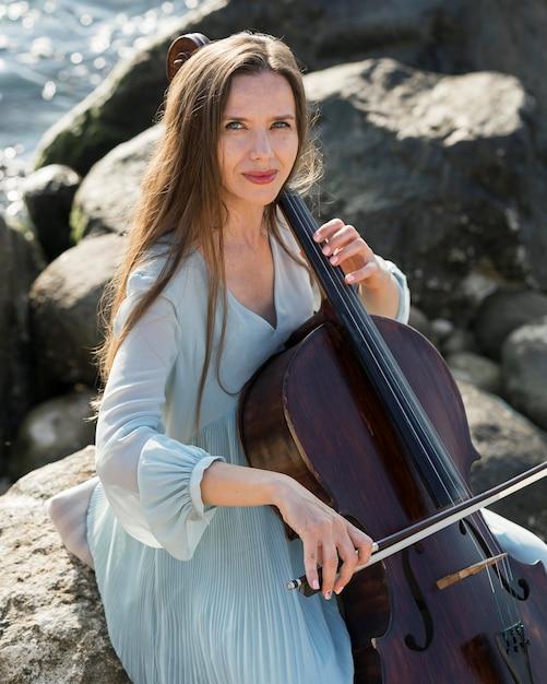 Kobieta Gra Na Wiolonczeli Nad Morzem Ze Skałami Darmowe Zdjęcia