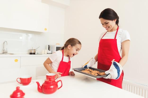 Kobieta I Dziewczynka W Czerwonych Fartuchach Pieczą Ciasteczka I Babeczki Premium Zdjęcia
