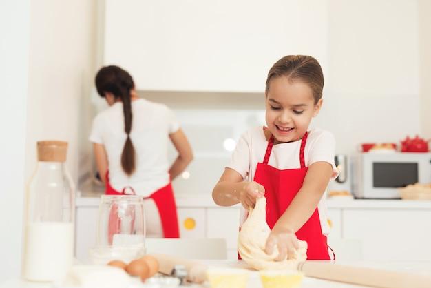 Kobieta I Dziewczynka W Czerwonych Fartuchach Pieczą Ciasteczka Premium Zdjęcia