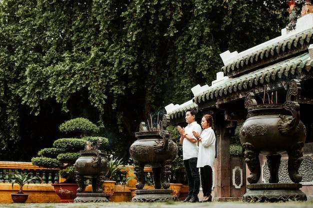 Kobieta I Mężczyzna Modlący Się W świątyni Z Płonącym Kadzidłem Darmowe Zdjęcia