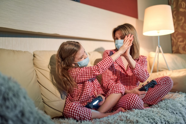 Kobieta I Młoda Dziewczyna W Piżamie I Medycznych Maskach Ochronnych Siedząca Na Kanapie W Salonie Z Kontrolerami Gier Wideo W Domu, Automatyczna Kwarantanna Izolacji, Covid-19. Premium Zdjęcia
