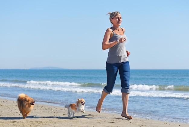 Kobieta i psy na plaży Premium Zdjęcia