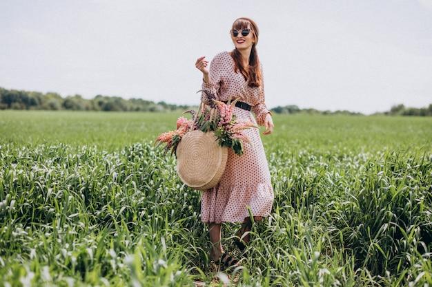 Kobieta idzie w polu z lupinuses Darmowe Zdjęcia
