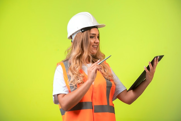 Kobieta Inżynier W Białym Kasku I Sprzęcie, Trzymając Listę Kontrolną I Poprawiając Ją. Darmowe Zdjęcia