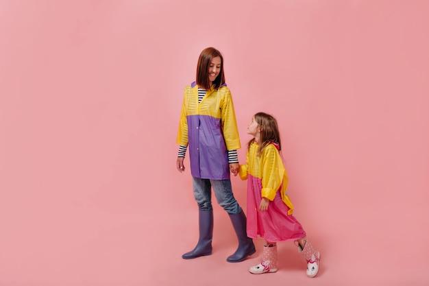 Kobieta Ja Z Cute Dziecko Dziewczynka W Płaszczach Przeciwdeszczowych. Matka, Córeczka Na Białym Tle Darmowe Zdjęcia