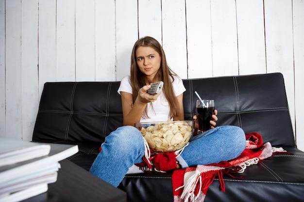 Kobieta Je Frytki, Pije Napoje Gazowane, Ogląda Telewizję, Siedzi Na Kanapie. Darmowe Zdjęcia