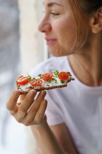 Kobieta Je żytni Chleb Chrupki Z Kremowym Tofu Z Wegetariańskim Serem, Pomidorem, Mikro Zieleniną. Zdrowe Jedzenie Premium Zdjęcia