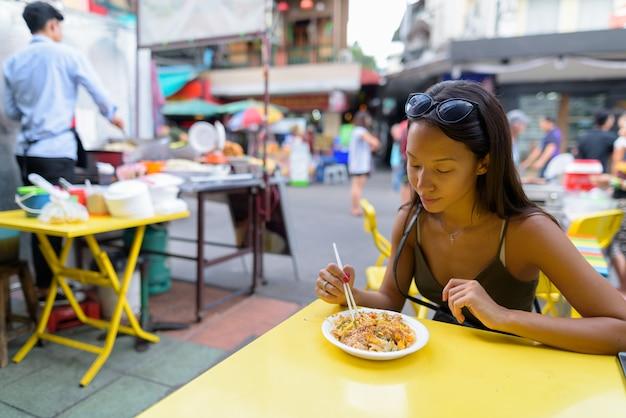 Kobieta Jedzenie Makaronu Pad Thai Przy Drodze Khao San Premium Zdjęcia