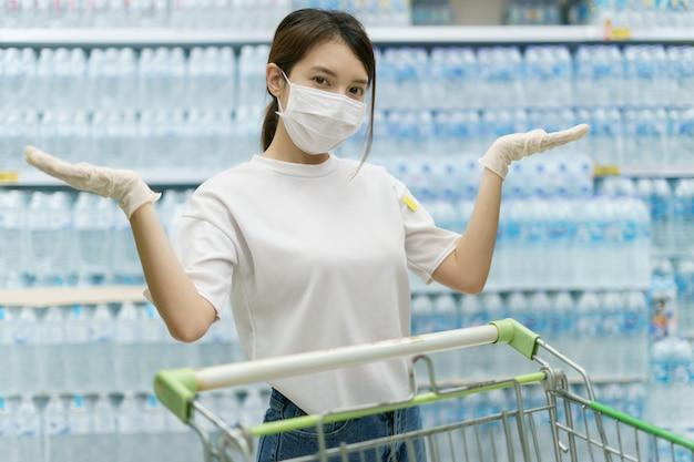 Kobieta Jest Ubranym Chirurgicznie Maskę I Rękawiczki Kupuje Wodę Pitną W Supermarkecie. Panika Po Pandemii Koronawirusa. Premium Zdjęcia