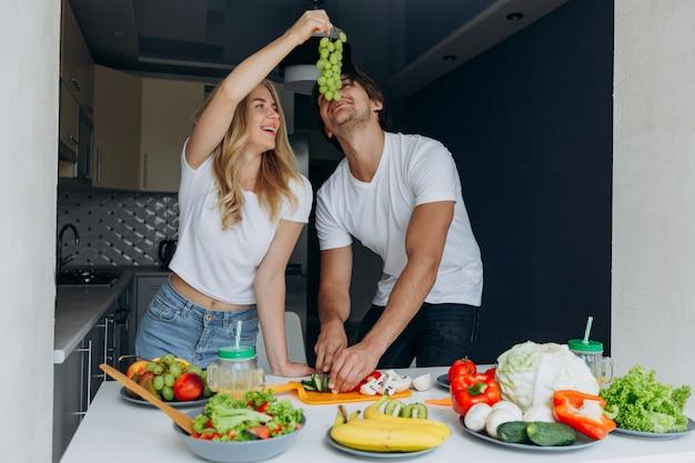 Kobieta karmi mężczyzna z winogronami podczas mężczyzna ciie warzywa Premium Zdjęcia