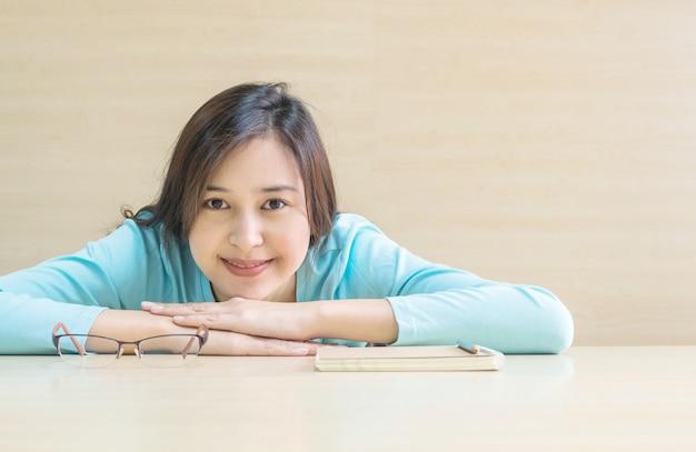 Kobieta kłamał na biurku z szczęśliwą twarz w odpoczynku od czytania książki Premium Zdjęcia
