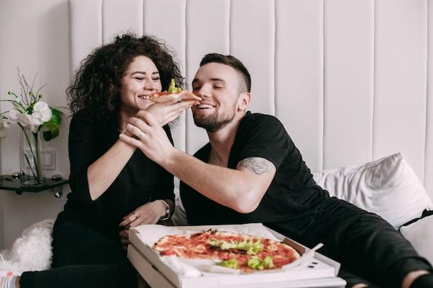 Kobieta kręcone daje kawałek pizzy do jej mężczyzny Darmowe Zdjęcia