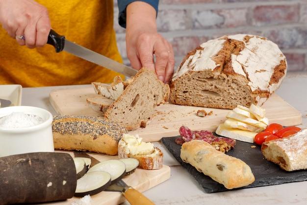 Kobieta kroi tradycyjny kromka chleba Premium Zdjęcia