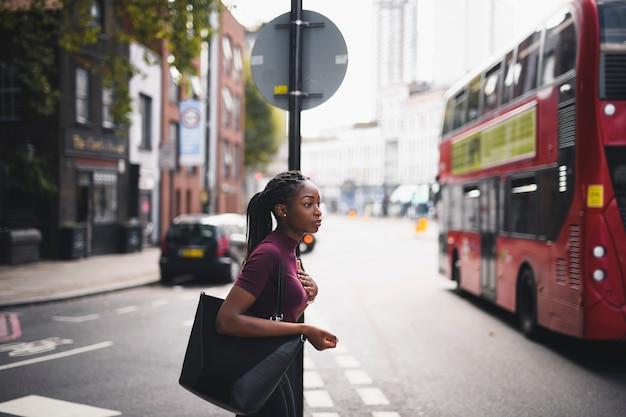 Kobieta krzyżuje ulicę ww centrum londyn z warkoczami Premium Zdjęcia