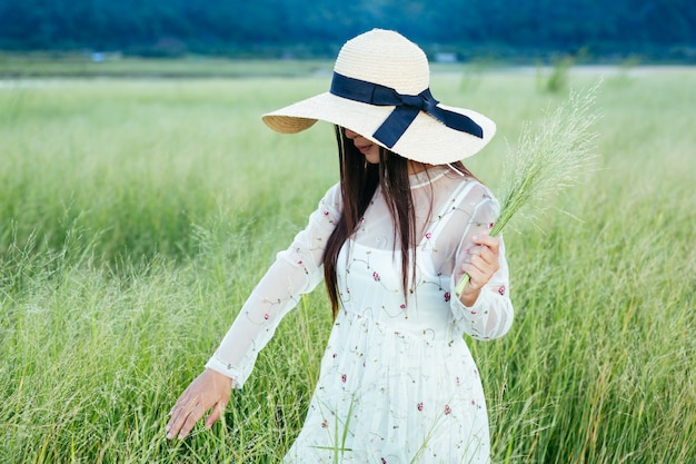 Kobieta, która trzyma trawę w dłoniach na pięknym polu trawy z górą. Darmowe Zdjęcia