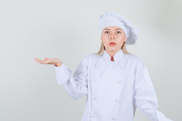 Kobieta Kucharz Gestykulująca, Jakby Trzymająca Coś W Białym Mundurze I Wyglądająca Na Zdezorientowaną Darmowe Zdjęcia
