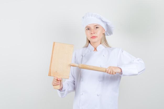 Kobieta Kucharz Trzyma Deskę Do Krojenia I Wałkiem Do Ciasta W Białym Mundurze I Wygląda Poważnie Darmowe Zdjęcia