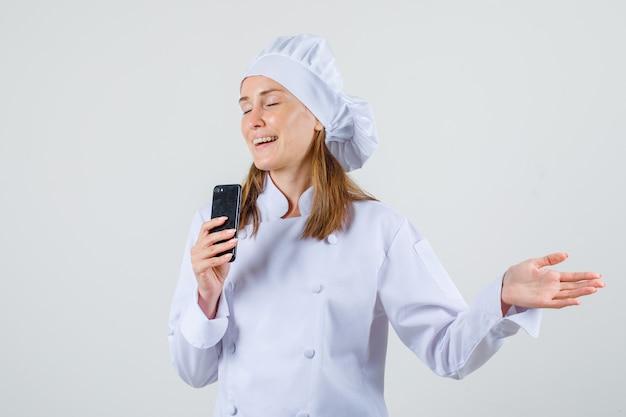 Kobieta Kucharz Trzyma Smartphone Z Otwartą Ręką W Białym Mundurze I Wygląda Wesoło Darmowe Zdjęcia