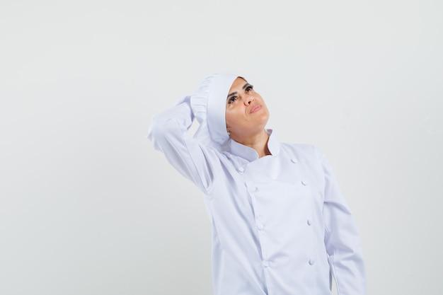 Kobieta Kucharz Trzymając Rękę Za Głową W Białym Mundurze I Marzycielski Wygląd Darmowe Zdjęcia