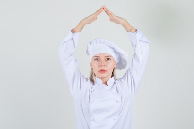 Kobieta Kucharz Trzymając Się Za Ręce Nad Głową Jako Dach Domu W Białym Mundurze Darmowe Zdjęcia