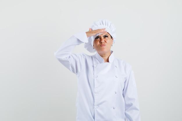 Kobieta Kucharz W Białym Mundurze, Patrząc W Górę Ręką Na Oczy Darmowe Zdjęcia