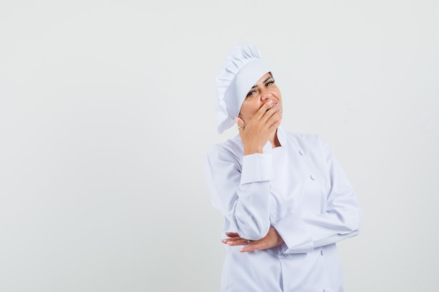 Kobieta Kucharz W Białym Mundurze, Trzymając Rękę Na Ustach I Patrząc Zaskoczony Darmowe Zdjęcia