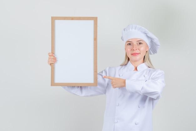 Kobieta Kucharz W Białym Mundurze, Wskazując Palcem Na Tablicy I Wyglądający Wesoło Darmowe Zdjęcia