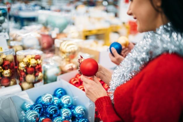 Kobieta Kupuje Bombki Choinkowe W Supermarkecie, Rodzinna Tradycja. Grudniowe Zakupy Artykułów świątecznych Premium Zdjęcia