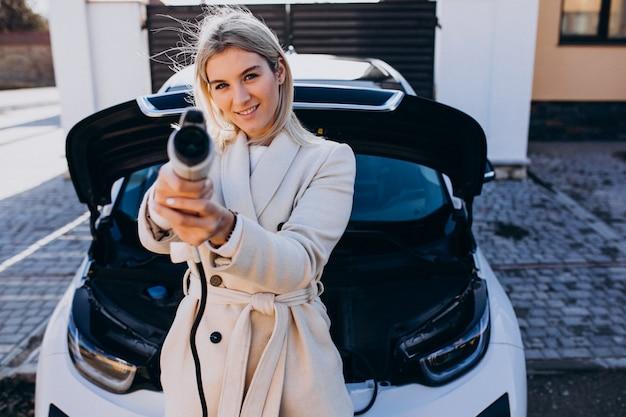 Kobieta ładuje electro samochód jej domem i trzyma ładowarkę Darmowe Zdjęcia