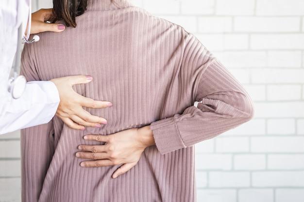 Kobieta Lekarz Bada Pacjenta Cierpiącego Na Ból Dolnej Części Pleców Premium Zdjęcia