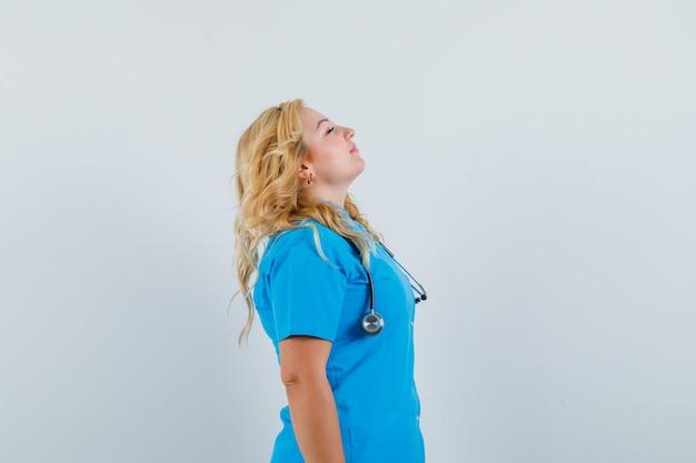 Kobieta Lekarz Bierze Głęboki Oddech W Niebieskim Mundurze I Wygląda Na Zrelaksowaną. . Darmowe Zdjęcia