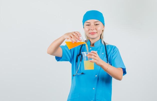 Kobieta Lekarz Mieszając Sok Przez Nalewanie I Uśmiechając Się W Niebieskim Mundurze Darmowe Zdjęcia