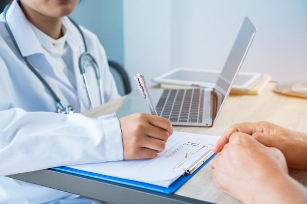 Kobieta lekarz pisania schowka recepty z papieru informacji rekordu Premium Zdjęcia