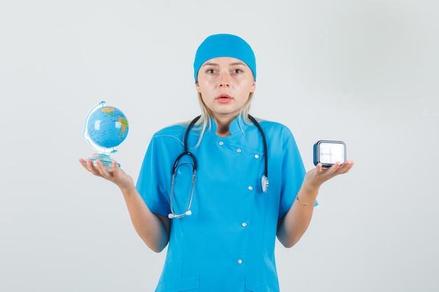 Kobieta Lekarz Posiadający światową Kulę Ziemską I Zegar W Niebieskim Mundurze I Patrząc Poważnie Darmowe Zdjęcia