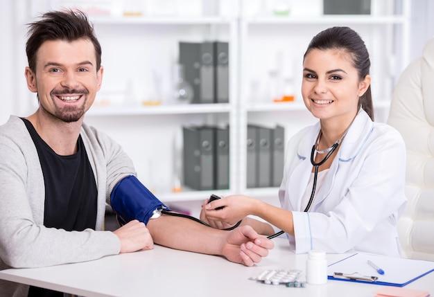 Kobieta lekarz sprawdza ciśnienie krwi pacjenta. Premium Zdjęcia