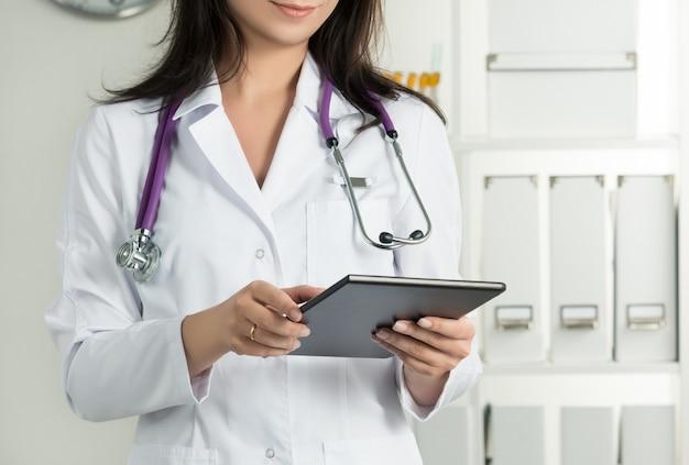 Kobieta Lekarz Trzyma Tablet Pc. Zbliżenie Dłoni Lekarza. Usługi Medyczne I Koncepcja Opieki Zdrowotnej. Premium Zdjęcia
