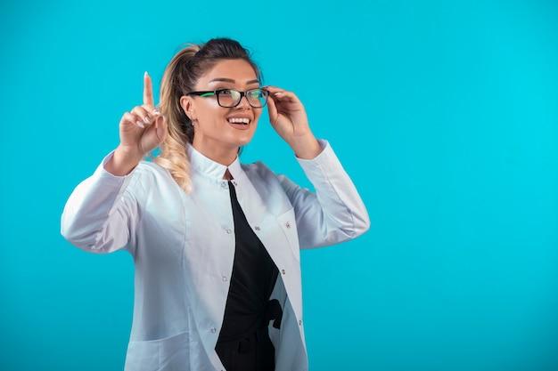 Kobieta Lekarz W Białym Mundurze Z Prośbą O Uwagę. Darmowe Zdjęcia
