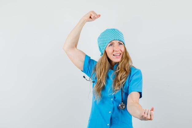 Kobieta Lekarz W Niebieskim Mundurze Pokazujący Gest Zwycięzcy I Wyglądający Błogo Darmowe Zdjęcia